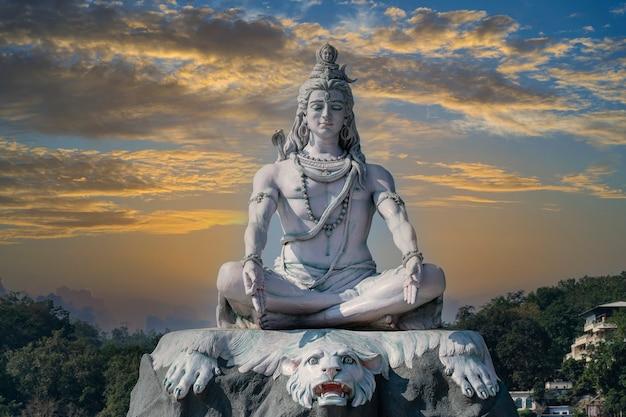 인도 리시케시(rishikesh) 마을의 갠지스 강(ganges river)에 있는 하늘과 구름에 대해 명상하는 힌두교 신 시바(shiva)의 동상이 닫혀 있다