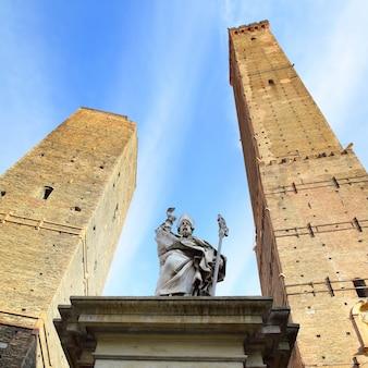 Статуя петрония и две древние башни в болонье, италия