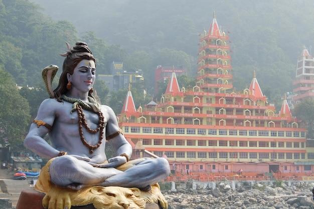 インドのリシケシのガンジス川の川岸で瞑想に座っているシヴァの像