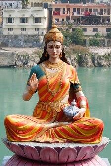 インドのリシケシのガンジス川の川岸に座っている女神パールヴァティーの像