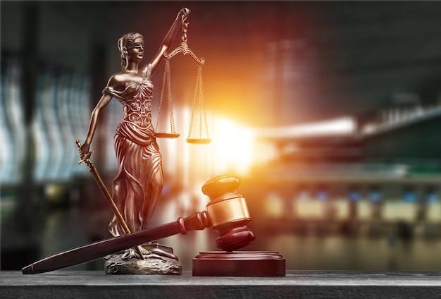 Статуя дамы правосудия с весами и молотком на столе