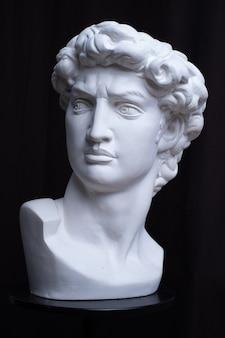 Статуя. на черном изолированном фоне. гипсовая статуя головы давида. мужчина.