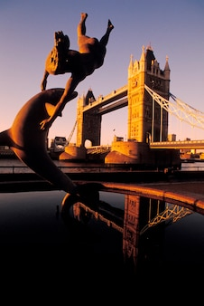 Statue and pool on riverbank with tower bridge in background, london, england