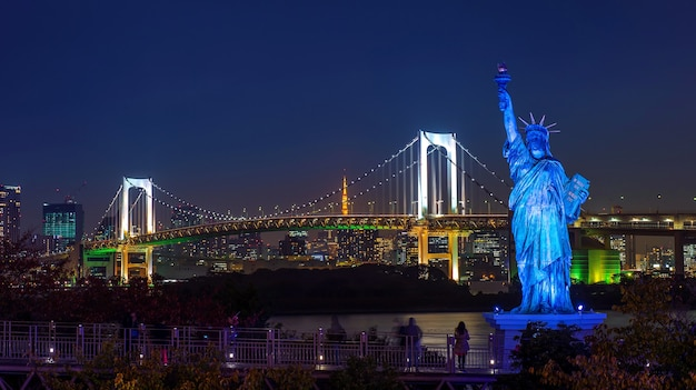 Statue and rainbow bridge at night, in tokyo, japan.