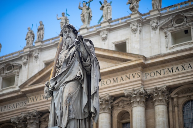Statue of saint peter and saint peter's basilica in st. peter's square, vatican city, rome, italy.