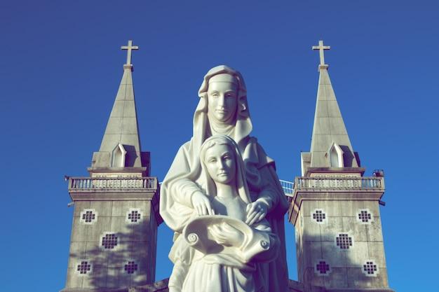 Статуи святой анны и девы марии стоят перед nongsaeng церковь является знаменитой католической церковью в таиланде