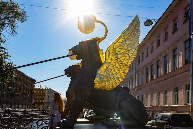 2020년 8월 상트페테르부르크 태양을 배경으로 은행 다리에 있는 날개 달린 사자 동상.
