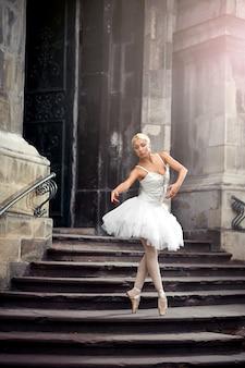 彫像のようなバレリーナ。古い城で練習しているすべての白を身に着けている若いバレリーナ