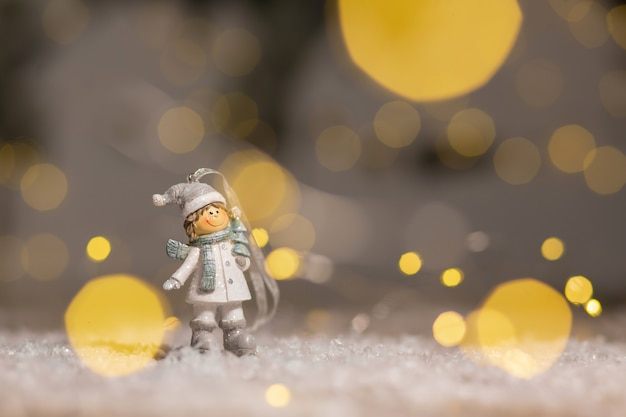 Statuette boy in knitted hats and scarves festive decor, warm bokeh lights.