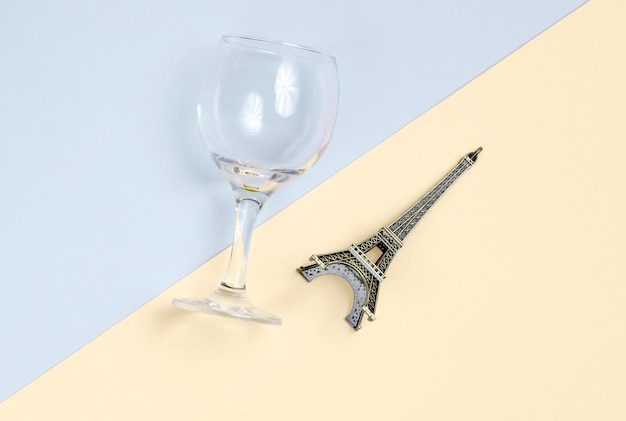 Statuette of the empire tower, empty wine glass on a gray-yellow paper background