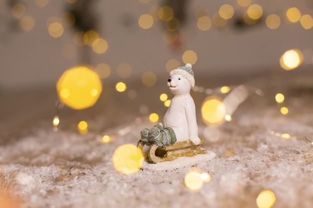Statuette of a polar bear sits on a wooden sled, in a knitted hat and socks festive decor, warm bokeh lights.