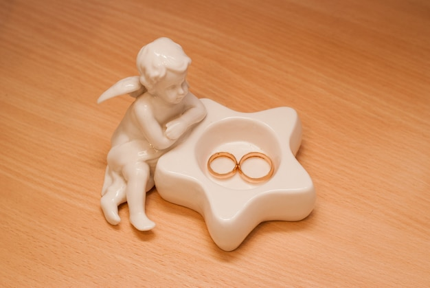 A statuette of a white angel. wedding set, wedding rings for the bride and groom. still life on a beige background.