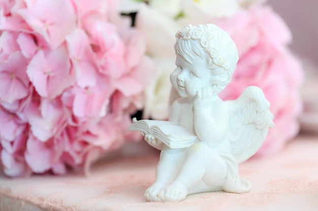 Statuette of a white sweet angel on a floral
