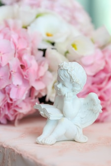 Statuette of a white sweet angel on a floral.