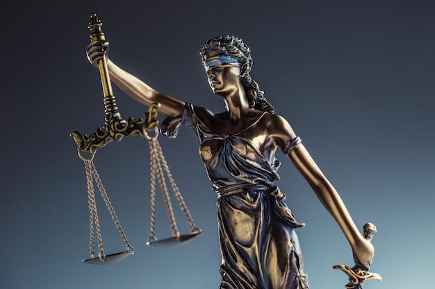 Статут правосудия. бронзовая статуя леди юстиции с весами и мечом.