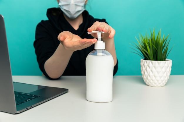 Оставайтесь дома и вымойте руки. женщина, сидящая за столом с мылом и ноутбуком.