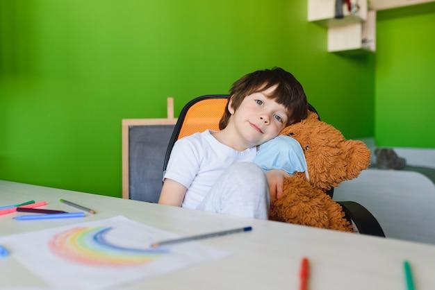 Оставайтесь дома из-за концепции пандемии коронавируса. крупным планом маленький мальчик рисует радугу на плакате оставаться дома