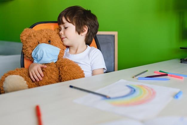 コロナウイルスのパンデミックの概念のため、家にいること。近くに小さな男の子が滞在する家のポスターに虹を描く