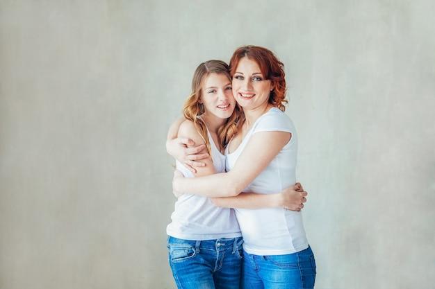 家のお母さんに滞在して、安全を確保してください。若い母親が子供を抱きしめます。女性と10代の少女が室内の灰色の壁の近くの白い寝室でリラックス。自宅で幸せな家族。若いお母さんが娘と遊ぶ。