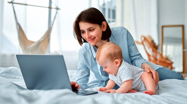 집에 머물면서 엄마는 노트북에서 원격으로 일하면서 아기를 돌 봅니다. 출산 휴가를 받고있는 젊은 어머니가 어린 아이와 함께 침대에서 일하려고합니다. 닫기, 복사 공간, 배경.