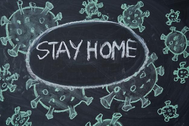 Останься дома. предупреждение о вспышке. написано белым мелом на доске в связи с эпидемией коронавируса во всем мире. текст пандемии covid 19 на черной предпосылке с открытым космосом. нарисованные вирусные бактерии