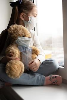 外出禁止令コロナウイルスのパンデミック予防。悲しい子供と彼のテディベアは両方とも保護医療マスクで窓辺に座って窓の外を見ています