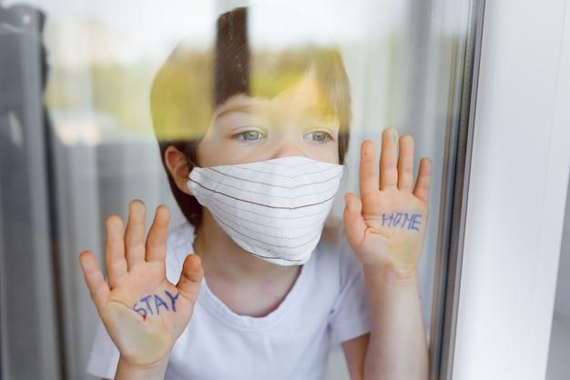 家にいて検疫コロナウイルスのパンデミック予防。窓の近くの防護マスクと窓の外を見て悲しい子