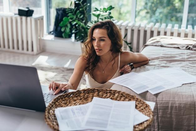 家にいる。床に座ってラップトップで作業している女性。
