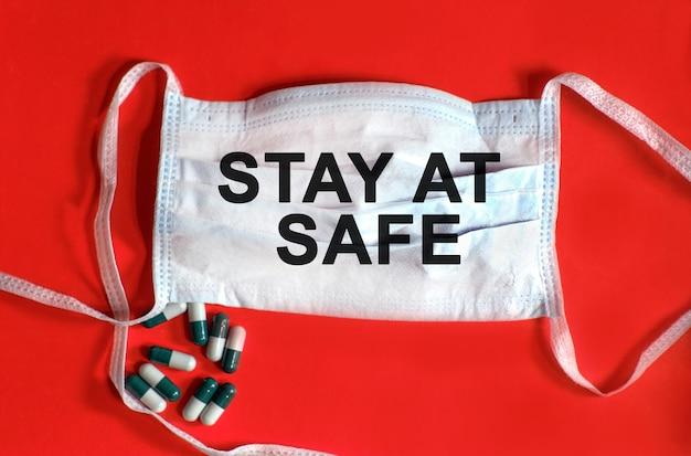 安全に滞在-保護フェイスマスクのテキスト、赤い背景のタブレット