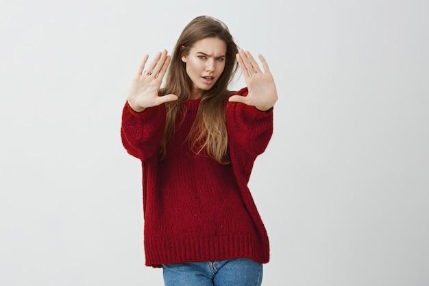 Stai lontano da me, bastardo. ritratto della donna popolare seria infastidita in maglione sciolto che tira le mani verso la macchina fotografica nella fermata o nel gesto sufficiente, essendo deluso o insultato