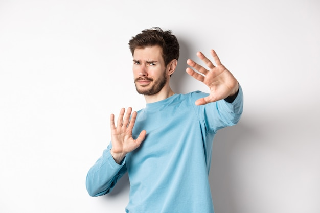 Stay away from me. reluctant young man step back with hands stretch out in defensive gesture, protecting himself, standing over white background