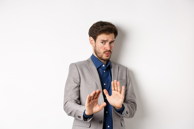 Stay away. reluctant businessman step back with concerned disgusted face, raising hands to block bad offer, rejecting something awful, telling no and decline proposal, white background.