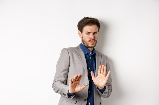 Stay away. reluctant businessman step back with concerned disgusted face, raising hands to block bad offer, rejecting something awful, tilting from disgust, white background.