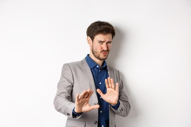 Держись подальше. неохотный бизнесмен отступает с озабоченным выражением лица, поднимает руки, чтобы заблокировать плохое предложение, отвергает что-то ужасное, говорит «нет» и отклоняет предложение, белый фон.