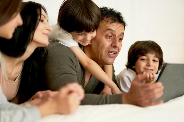 침대에 누워 디지털 태블릿을 사용하여 어린 아이들과 함께 행복한 라틴 가족을 연결하세요