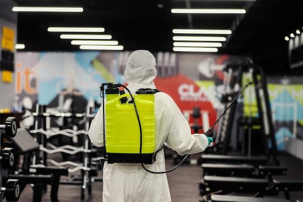 Covid 19の健康警告を維持する保護服を着た男性は、感染の拡大を防ぎます