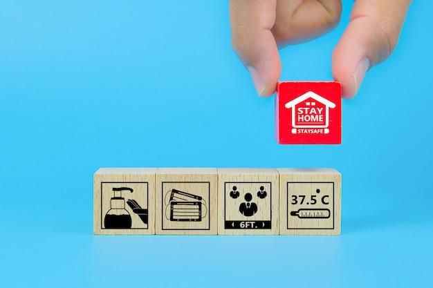 Пребывание дома и значок предупреждения covid-19 на деревянном игрушечном блоке.