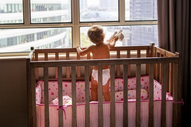 おもちゃの猫と一緒に家にいる赤ちゃんはベビーベッドに立って、高層ビルの街並みの窓の外を見ています