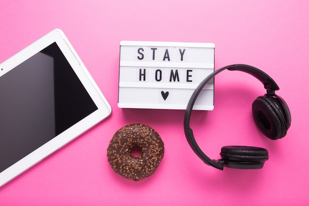 Stay home, boxing inscription. remote online work at home. headphones tablet and diary on a pink wall.