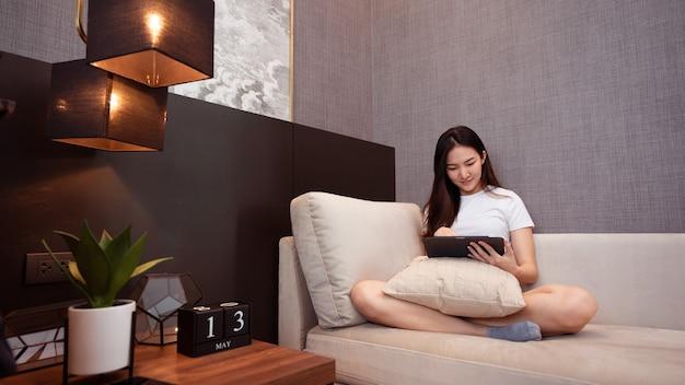 Оставайтесь дома, девушка в белой футболке сидит на уютном большом диване в хорошо оформленной гостиной.