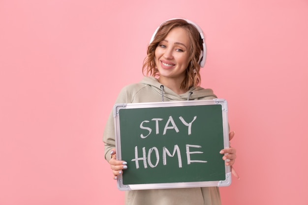 Stay home concept positive message woman with headphones dressed oversize hoodie holds chalkboard with the words stay home.