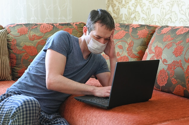 Stay at home concept. quarantine due coronavirus pandemic. business man working from home, wear a protective mask. remote work.