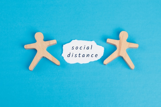 Stay at home concept with social distance text on torn paper, wooden figures on blue table flat lay.