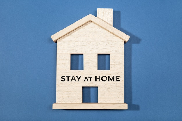 Stay at home concept. wooden house icon isolated on blue surface. coronavirus outbreak advice