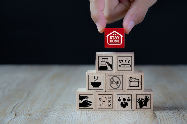 Stay home and covid-19 icon on wooden toy block. concepts for health and medical protect of coronavirus infection.