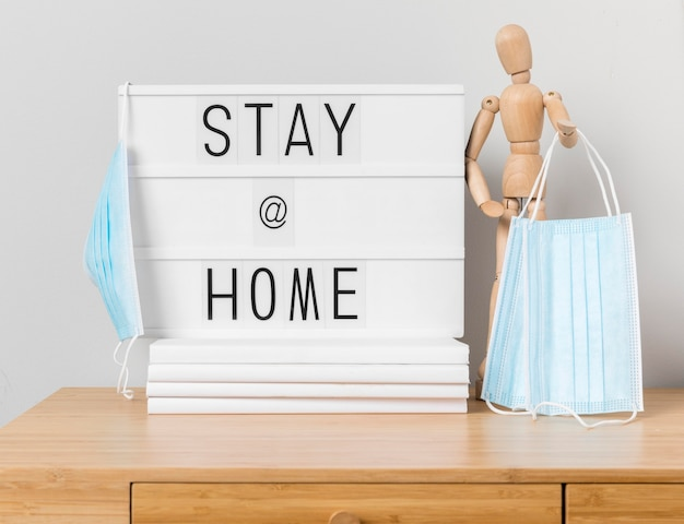Stay at home inscription with wooden mannequin and medical masks