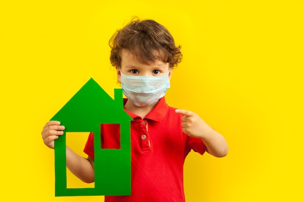 Stay home. a masked boy holds a green house model in his hands and points a finger at it.