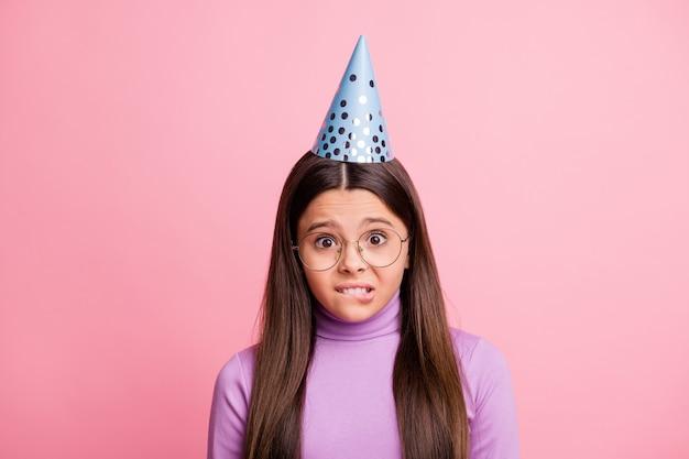 Остаться дома вечеринка отменить концепцию взволнованная маленькая девочка в головном уборе на день рождения кусает зубы губами, изолированными на фоне пастельных тонов
