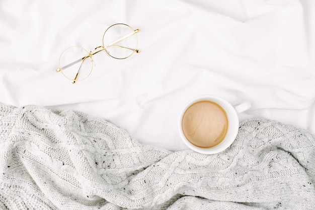 Stay home, quarantine. cup of coffee on bed with warm plaid. copy space. flat lay, top view