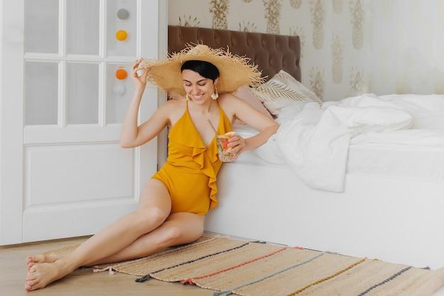 Оставайся дома, на карантин. отпуск отменен. молодая женщина в желтом купальнике на кровати в гостиничном номере.
